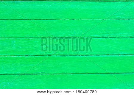 Texture of bright green wooden planks with some spaces between them