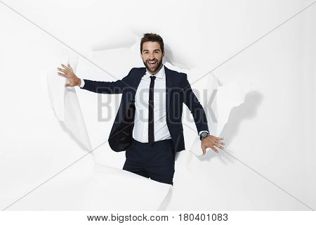 Successful businessman emerging from torn page portrait