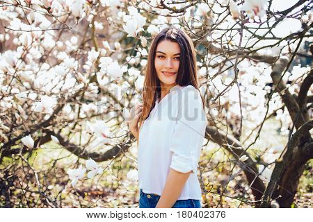 Spring Portrait Of Happy Woman Standing On Background Magnolia Blossoming Flowers. Spring Season