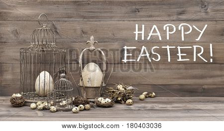 Easter decoration with eggs nest and birdcage. Vintage style composition with handwritten text Happy Easter