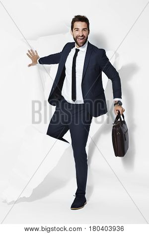 Happy Businessman bursting out of white background