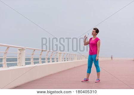 Fitness woman drinking water after running at the promenade by the sea. Thirsty sport runner resting taking a break with water bottle drink outside after training. Beautiful fit sporty girl.