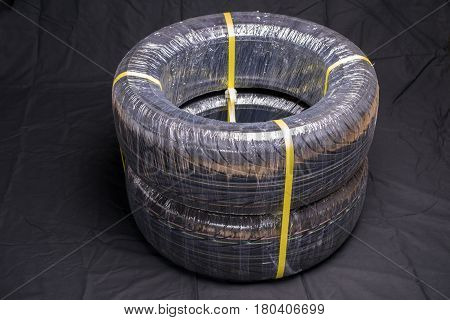 Two packing automobile tires on black cloth