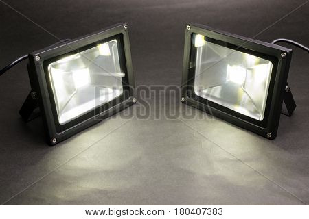 Two LED floodlights emitting on dark paper