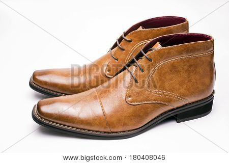Sideways brown chukka boots on a white background
