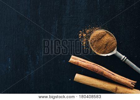 cinnamon and cinnamon sticks on a black background