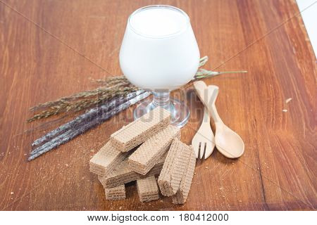 cocoa waffers and milk in glass isolated on wooden table