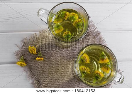 Two cups of herbal tea with coltsfoot (or Tussilago) flowers top view