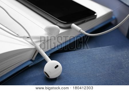 Audiobook concept. Open book and mobile phone with earphones, closeup