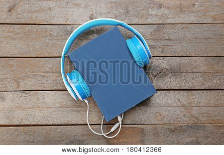 Audiobook concept. Hardcover book and headphones on wooden background