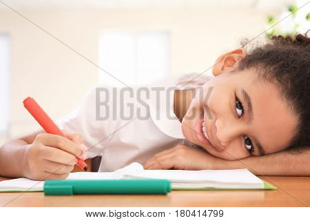 Portrait of beautiful African elementary schoolgirl learning in classroom