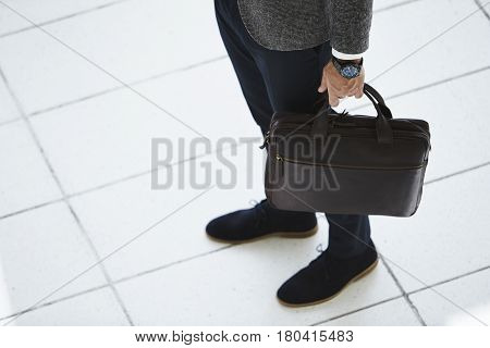 Briefcase guy wearing wristwatch low section studio shot
