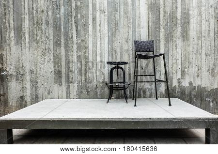 short circle and long square metal chairs on the stage with cement wall background stand by or lonele concept