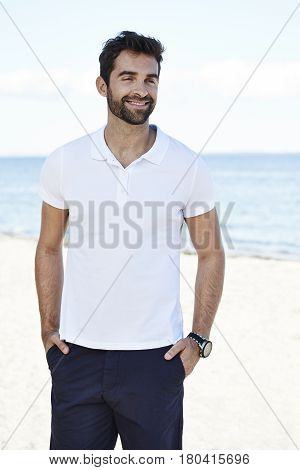 Handsome Guy smiling on beach looking away