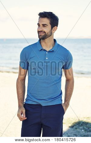 Guy in blue polo shirt on beach smiling