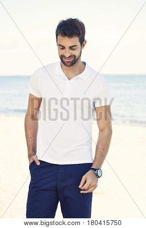 Man on holiday smiling on beach lucky him