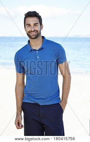 Happy dude in blue on beach portrait