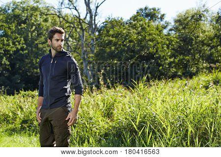 Man standing outdoor in field looking away