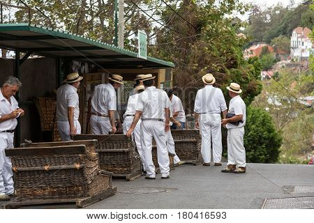 FUNCHAL PORTUGAL - SEPTEMBER 2 2016: Toboggan riders moving traditional cane sledge downhill on the streets of Funchal. Monte park Madeira island Portugal
