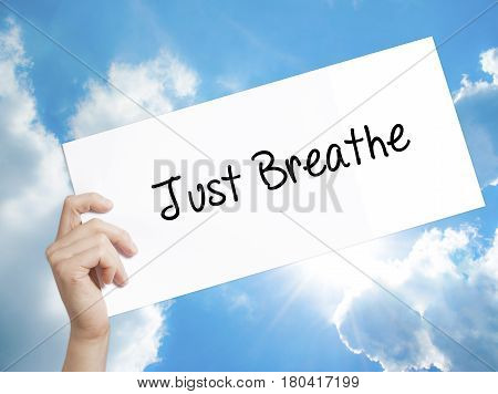 Just Breathe Sign On White Paper. Man Hand Holding Paper With Text. Isolated On Sky Background