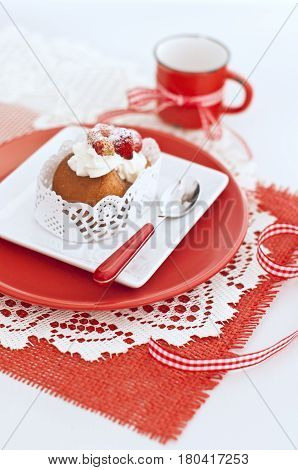 Italian cake baba with a cream and strawberries in white and red plates red cup with ribbon on napkin on wooden board
