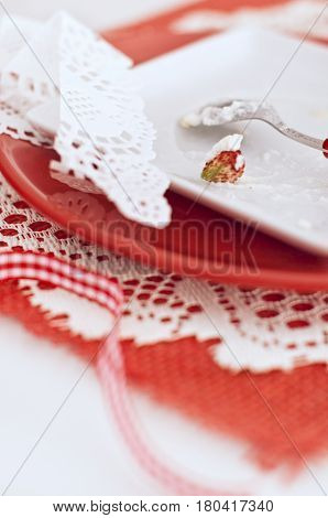 Remains of baba with a cream and strawberries in white and red plates on napkin on wooden board