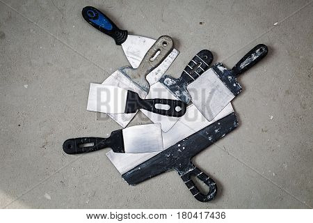 lot of construction spatulas on the cement floor