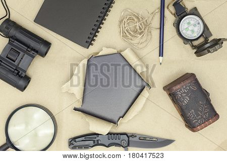 binoculars pocket knife, compass, paper, note, pencil, and magnifier on brown paper and torn paper background