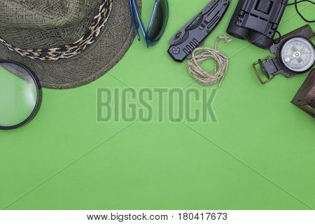 Pocket knife with compass, hat, glasses, rope, and magnifying glass on green background.