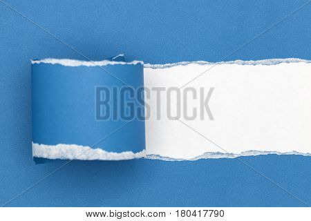 Blue ripped open paper on white paper background