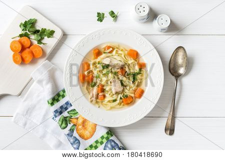Fresh chicken soup with vegetables and pasta in a bowl with carrot and parsley on white table top view