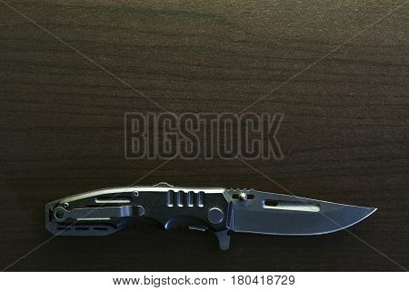 Pocket knife on black wood background. .