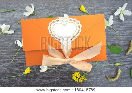Orange gift envelope tied with a pink ribbon on wooden background with flowers.