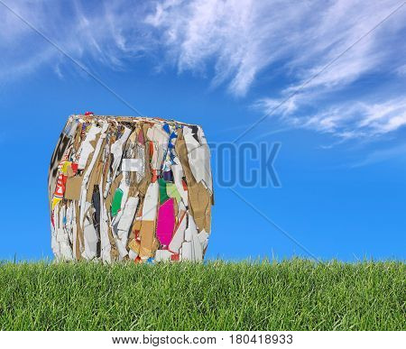 Pressed boxes made of paperboard on the meadow with blue sky in the background