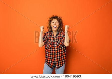 Young Natural Curly Woman Standing Over An Orange Background Being Very Excited