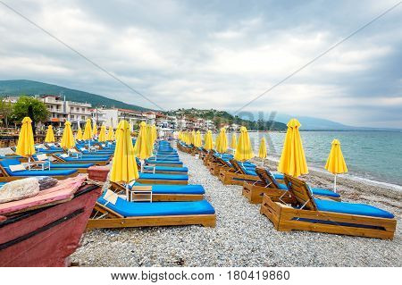 Beach umbrellas and empty lounge chairs on a cloudy day. Platamonas Pieria Macedonia Greece