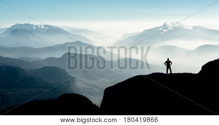 Beautiful view snow covered mountain ranges silhouettes and fog filled valleys with bright back light. South Tyrol, Itay, Alps. Happy winning success man at sunset or sunrise standing relaxed and is happy for having reached mountain top summit goal during