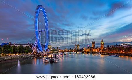 LONDON UNITED KINGDOM - OCTOBER 6 2014: London Eye and Westminster Palace in London. The largest Ferris Wheel in Europe structure of the London Eye is 135 meters tall and 120 meters in diameter.