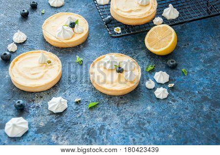 Individual Lemon Curd Tarts With Blueberry Jam Meringue Basil Leaves On A Blue Rusty Background. Fla