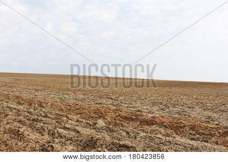 Rough plough field with sky and clouds