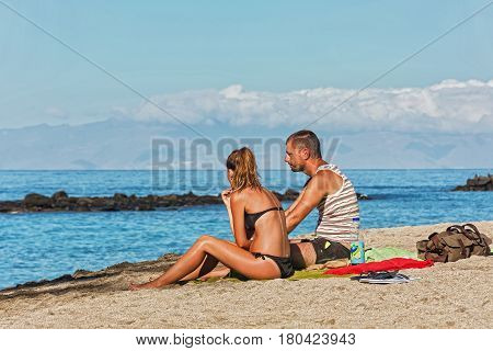 Spain the island of Tenerife - 22.09.2016: On the sandy shore of the sea sit a man and a woman
