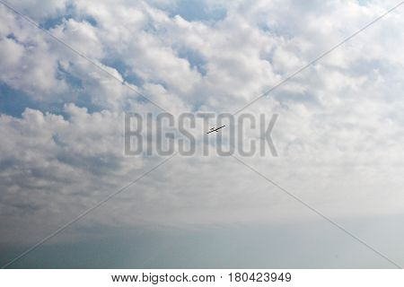 Glider on blue sky with clouds and sunshine