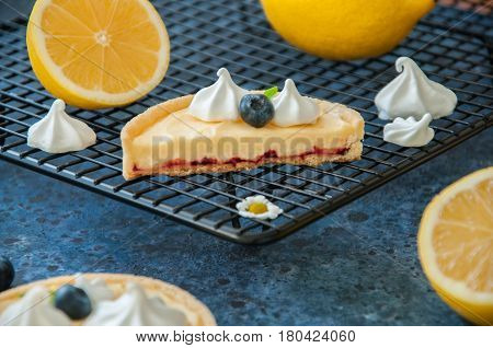 Whole And Slice Of Individual Lemon Curd Tarts With Blueberry Jam Meringue And Basil Leaves On A Blu
