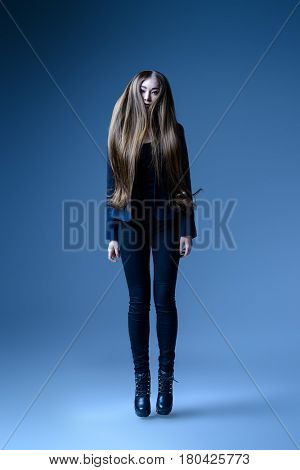 Vogue shot. Full length portrait of a fashionable model with beautiful long hair posing at studio in a motion.