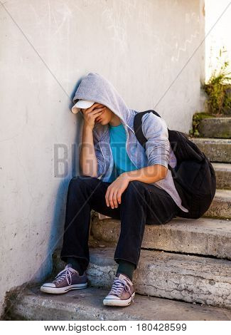 Sad and Troubled Teenager sit on the Stairs outdoor