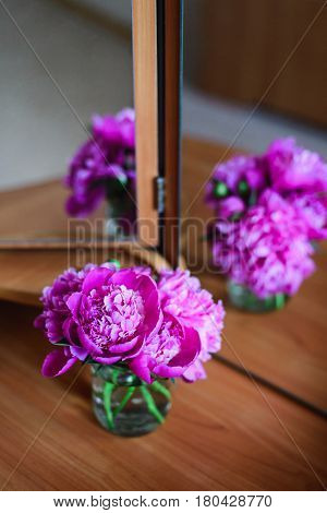 close-up pink peonies in glass jar on table with mirror reflection congratulations for everyday concept