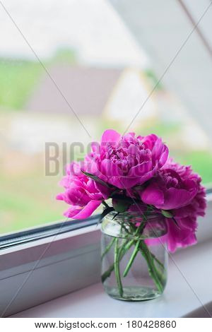 pink peonies bouquet in glass jar on white window sill on house background