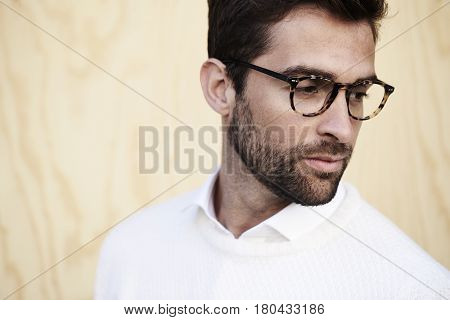 Man with stubble and spectacles looking away