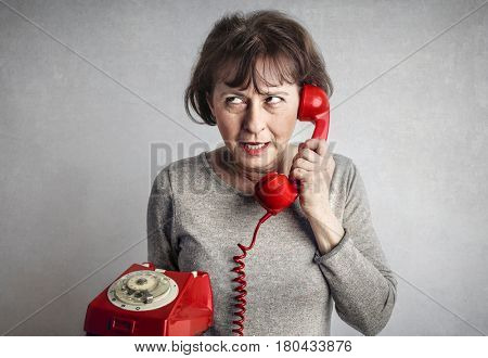 Woman using a red old fashioned telephone