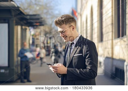 Young man in elegant clothes using a smartphone
